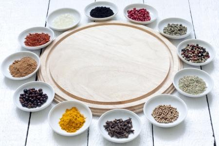 legumbres secas: Las especias y legumbres secas con una tabla de cortar en tablones blancos Foto de archivo