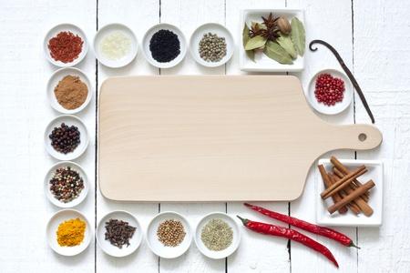 Specerijen en gedroogde groenten met snijplank op witte planken Stockfoto