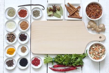 Spices and dried vegetables with cutting board on white planks Standard-Bild
