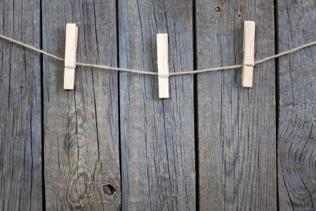 peg board: Clothespins on rope and empty vintage wooden planks background