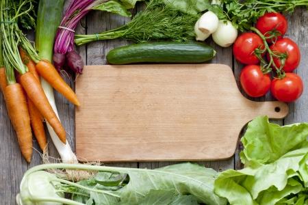 Veel verse biologische groenten en lege snijplank achtergrond
