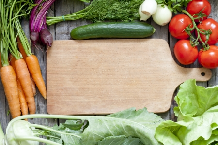 Many fresh organic vegetables and empty cutting board background  photo