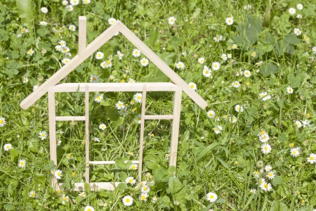 Wooden home in spring green grass ecological building concept photo