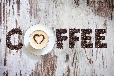 Tasse Kaffee mit Bohnen auf Buchstaben vintage retro-Boards