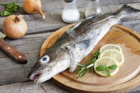 hake: Cod raw fish on cutting board in the kitchen with spices Stock Photo