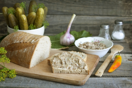 canned meat: Bread lard and pickles on old vintage cutting board still life
