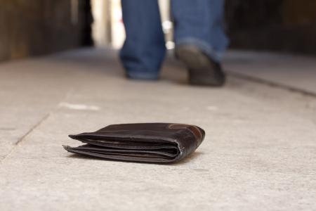 Verlorene Geldbörse auf der Straße und die Beine des Mannes zu Fuß Konzept