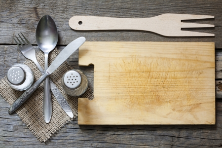 Cutlery and vintage empty cutting board food background concept photo
