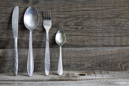 vintage cutlery: Cutlery kitchenware on old wooden boards background food concept