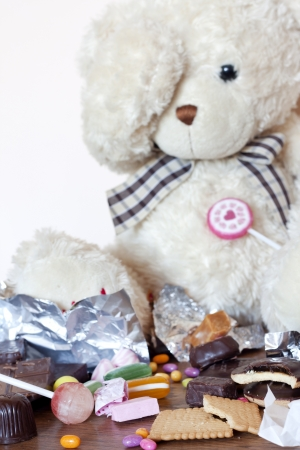 Addiction of eating sweets creative concept with teddy bear photo