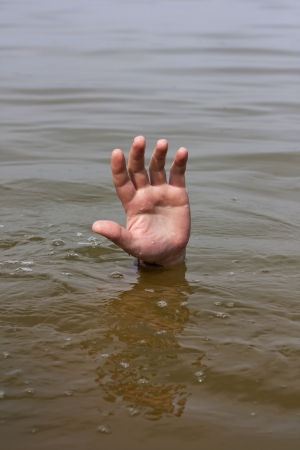 Hand of drowning man waits for help in the lake photo