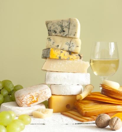 queso: Pila de queso muchos diferentes tipos de vino con uvas y nueces Foto de archivo