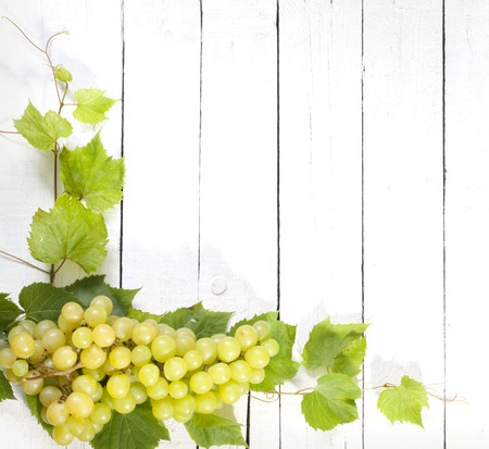 Grapes and leaves on vintage white planks background photo
