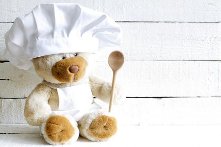 gorro chef: Osito de peluche en el sombrero del cocinero con el alimento abstracto cuchara Foto de archivo