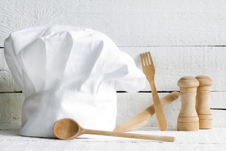 Chef hoed en houten keukengerei voedsel abstract op witte borden Stockfoto