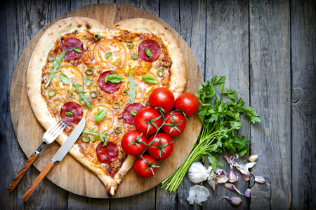 Pizza heart shape with cheese and tomato on vintage boards Standard-Bild