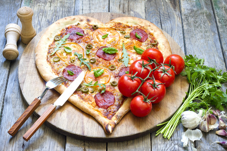 Pizza heart shape with cheese and tomato on vintage boards Stock Photo