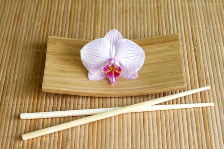 japones bambu: Las orquídeas en estera de bambú abstracto comida asiática concepto único Foto de archivo