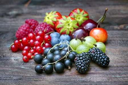 Summer wild berry fruits on vintage board still life concept photo