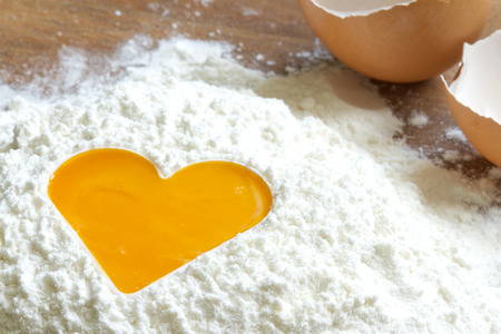 preperation: Yolk egg in flour love baking concept Stock Photo