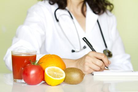 healthy lifestyle: M�dico especialista en nutrici�n en el cargo con frutos sanos concepto de dieta