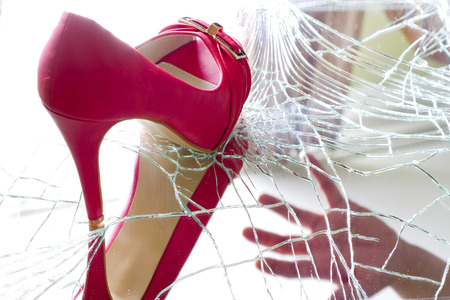 debility: Angry and bad woman concept with shoe and broken mirror Stock Photo