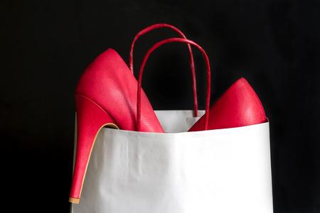 comprando zapatos: Los tacones altos zapatos rojos en bolsa de la compra contra el negro Foto de archivo
