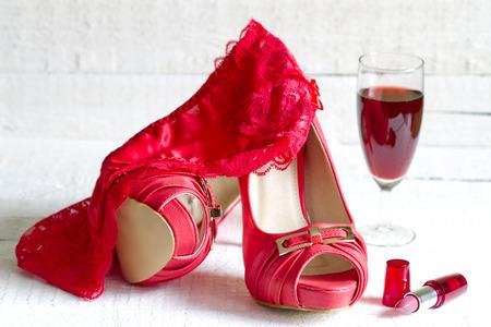 Hoge hakken en rode g-string abstract concept op witte borden Stockfoto