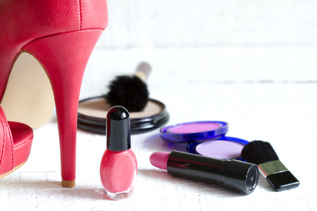 High red heels and set of cosmetics abstract on white planks photo