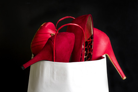 High heels red shoes in shopping bag against black Stock Photo