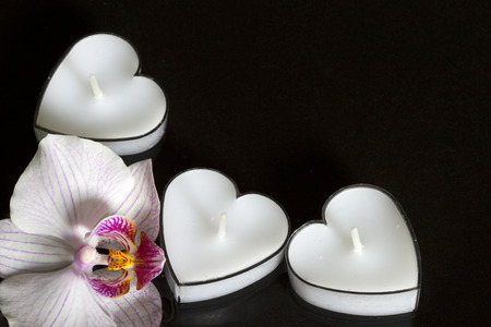 lustful: Candles hearts with orchid on black background love concept