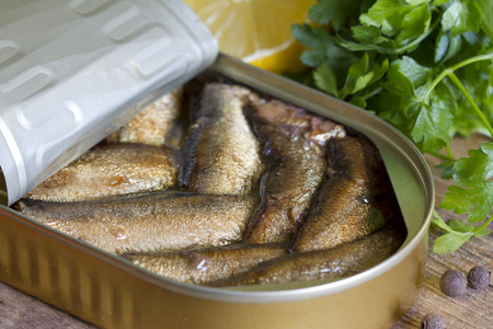tin can: Sprats with oil in tin can on wooden board