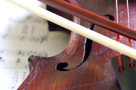 Violin bow on musical strings closeup Stock Photo