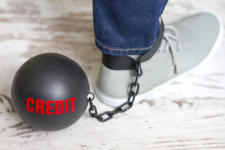 metal ball: In slavery of credit concept with metal ball on chain and leg Stock Photo