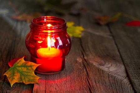 Begraafplaats rode lantaarn kaars met herfstbladeren in de nacht
