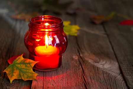 candles: Cemetery red lantern candle with autumn leaves in night