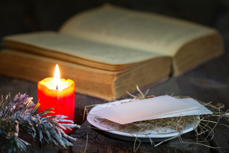 bible christmas: Bible and christmas red candle on the table by night Stock Photo