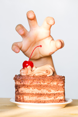 greediness: Greed for sweets concept with hand and chocolate cake Stock Photo