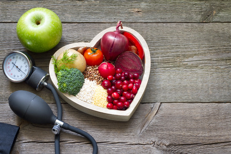 Healthy food in heart and cholesterol diet concept on vintage boards Standard-Bild