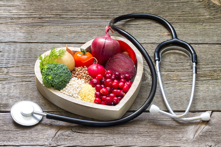 stethoscope: Healthy food in heart and cholesterol diet concept on vintage boards Stock Photo