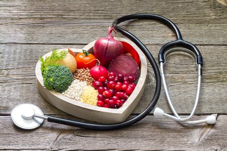salud y deporte: La comida sana en el corazón y colesterol dieta concepto en los tablones de la vendimia Foto de archivo