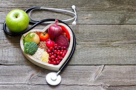 estetoscopio: La comida sana en el coraz�n y colesterol dieta concepto en los tablones de la vendimia Foto de archivo