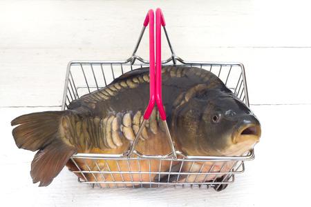 Karper ruwe verse vis in de het winkelen mand op witte houten vloer
