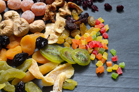 candied fruits: Candied dried mixed assortment of exotic fruits on black marble