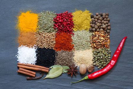 Spices and herbs on black marble abstract background Foto de archivo
