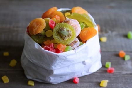 Gekonfijte vruchten in witte zak closeup op houten planken