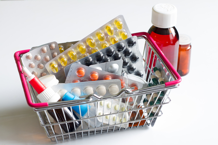 toxic substance: Shopping basket full with pills and medicines on a white background