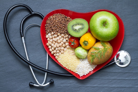 Healthy food on red heart plate cholesterol diet concept