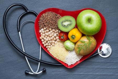 estetoscopio corazon: La comida sana en concepto de dieta de colesterol placa de corazón rojo Foto de archivo