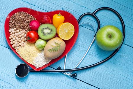 salud: Comida en el plato corazón con el estetoscopio concepto de cardiología Foto de archivo